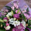 Bouquet of pink and purple flowers with assorted green fronds